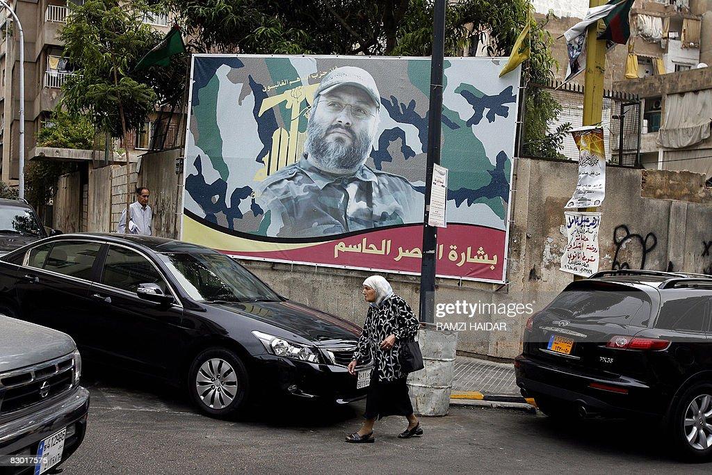 A Lebanese woman walks past a billboard bearing a portrait of slain Lebanese Hezbollah military leader Imad Mughniyeh in Beirut on September 26 2008...
