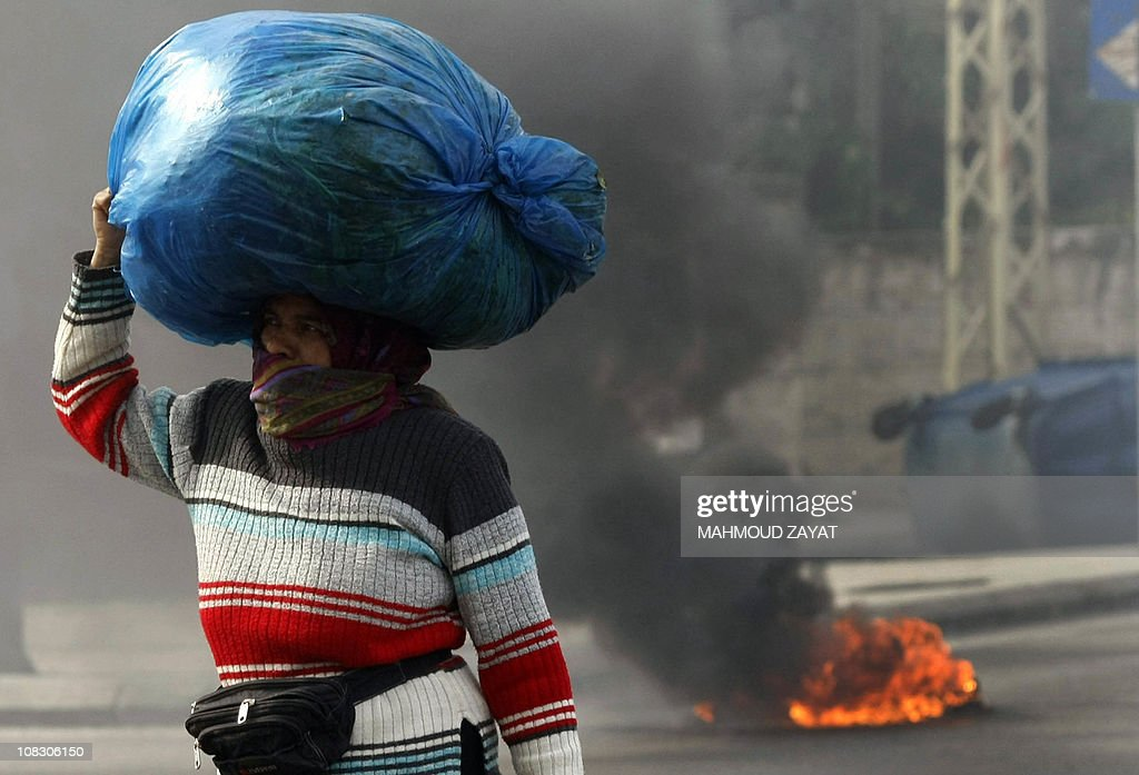 A Lebanese woman walks past a burning tire during a demonstration in support of the caretaker prime minister Saad Hariri on the outskirts of the coastal city of Sidon, south of Beirut on January 25, 2011, as hundreds of people converged on the northern city of Tripoli to take part in a 'day of rage' over the likely appointment as prime minister of Hezbollah-backed tycoon Najib Mikati.