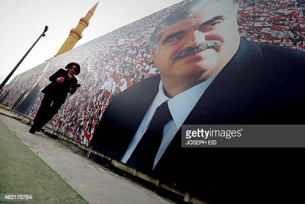 A Lebanese woman walks past a giant poster showing slain Lebanese prime minister Rafiq Hariri on February 6 2015 in central Beirut on the tenth...