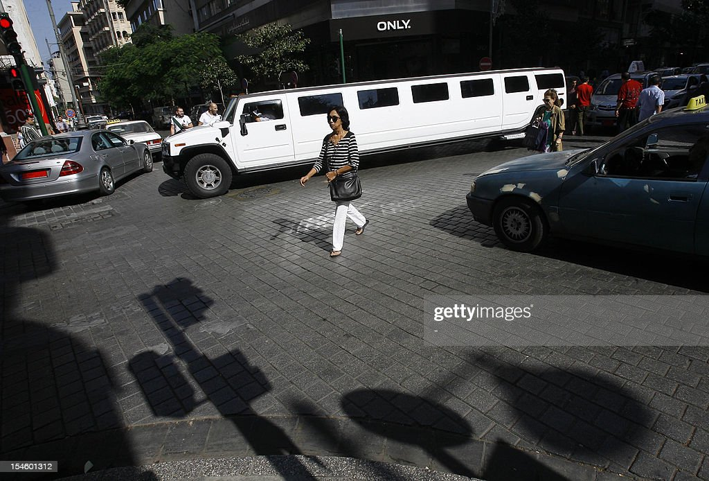 A Lebanese woman walks past cars driving on Hamra Street in Beirut on October 23, 2012 as life returned to normal, days after a car bomb blast in the Lebanese capital. The Lebanese army said it was determined to restore order in the country which has been roiled by growing political tensions linked to neighbouring Syria.