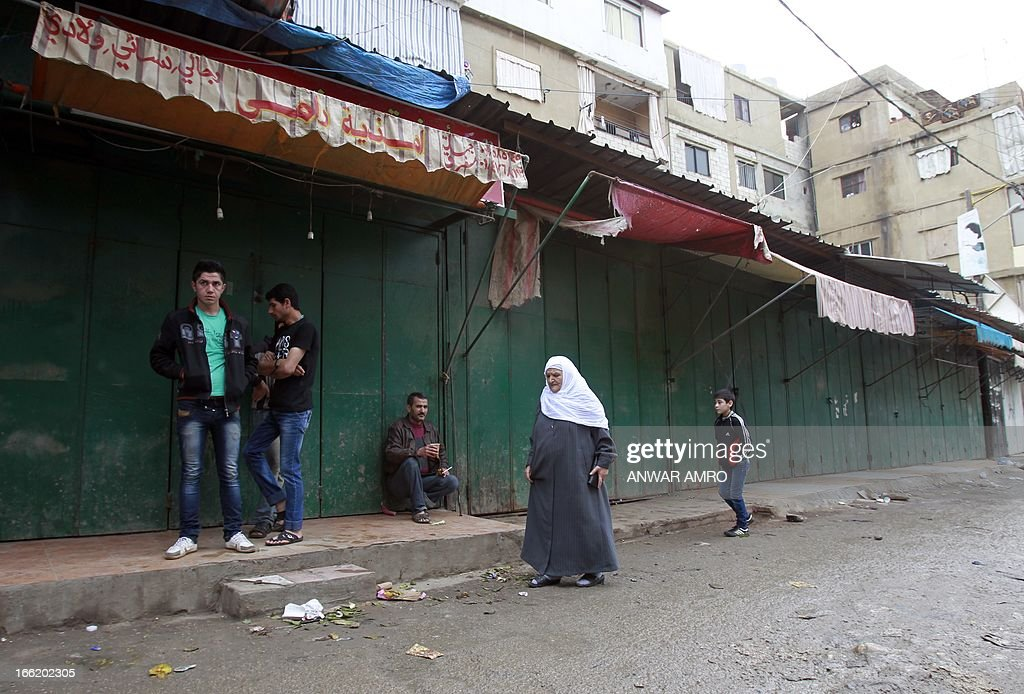 A Lebanese woman walks past closed shops owned by Syrian nationals at the Shiite dominant neighbourhood of Hay al-Selloum in a Beirut southern suburb on April 10, 2013. The shops were forced to close by the families of 11 Lebanese Shiite pilgrims abducted in northern Syria last year and still awaiting for their release.