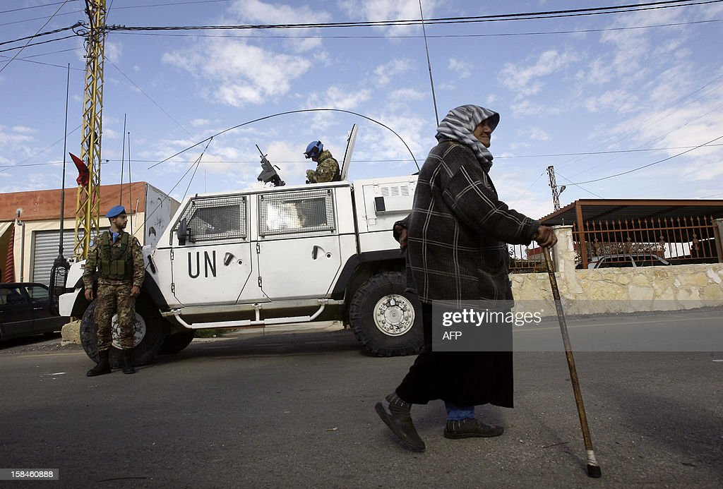 A Lebanese woman walks past Italian peacekeepers of the United Nations Interim Force in Lebanon (UNIFIL) in the southern Lebanese village of Tair Harfa on December 17, 2012. An Israeli missile fired during the 2006 summer war between Israel and Lebanon's Hezbollah exploded in the village, causing material damage, according to a Lebanese security source. AFP PHOTO/MAHMOUD ZAYYAT