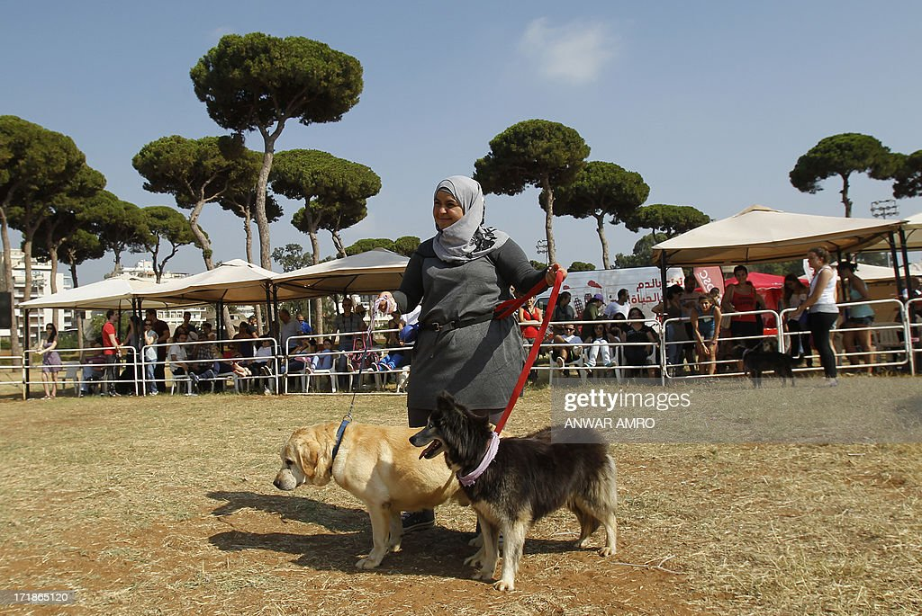 A Lebanese woman walks with her dogs in the arena during the Beirut for the Ethical Treatment of Animals (BETA) dog show in Beirut, which holds contests to name 'best dog', 'cutest puppy', and 'best dog costume' in addition to 12 other categories on June 29, 2013. The show is one of BETA's major fundraisers to try to improve the welfare of animals in the region and to stop the abuse against them.