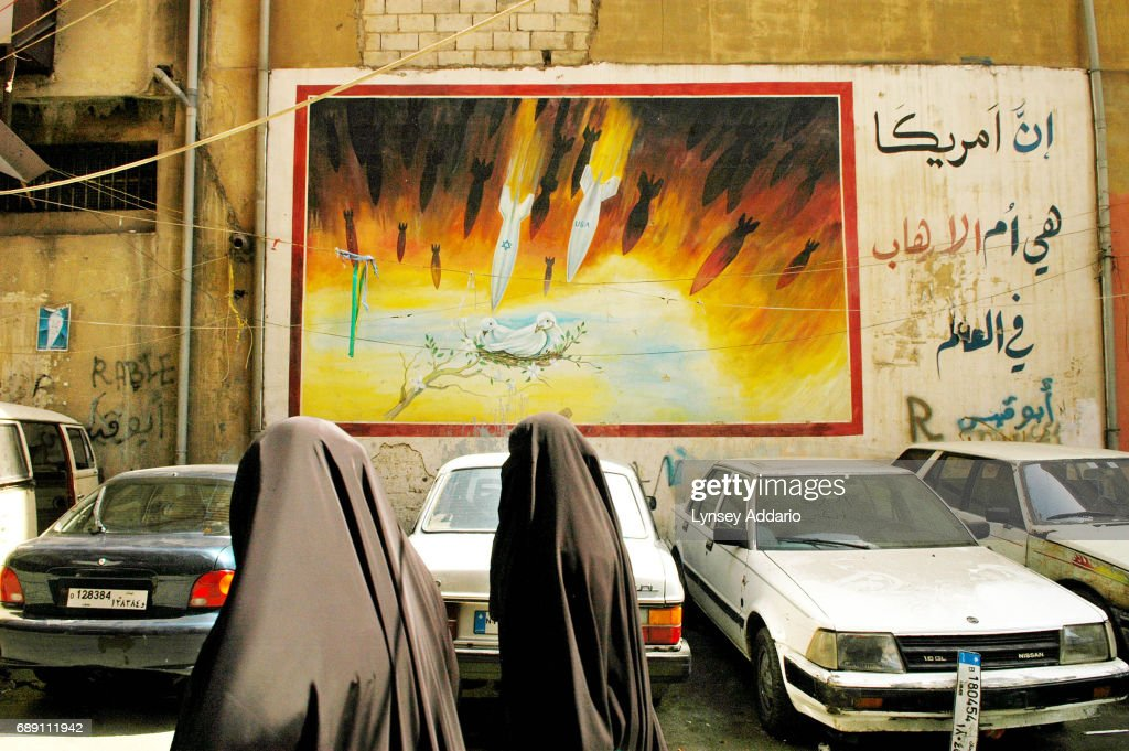 A Lebanese woman waslks past an anti-American and Israeli mural in Beirut's southern suburbs, in Lebanon, September 19, 2006. As more and more United Nations troops get situated across southern Lebanon, Israel has allegedly agreed to pull out all troops remaining since the ceasefire in August as early as this weekend.