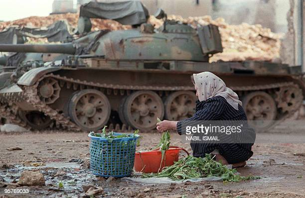 Lebanese woman who lives on the PortNormandy green line between East and West Beirut washes vegetables near her house 25 January 1989 behind a...