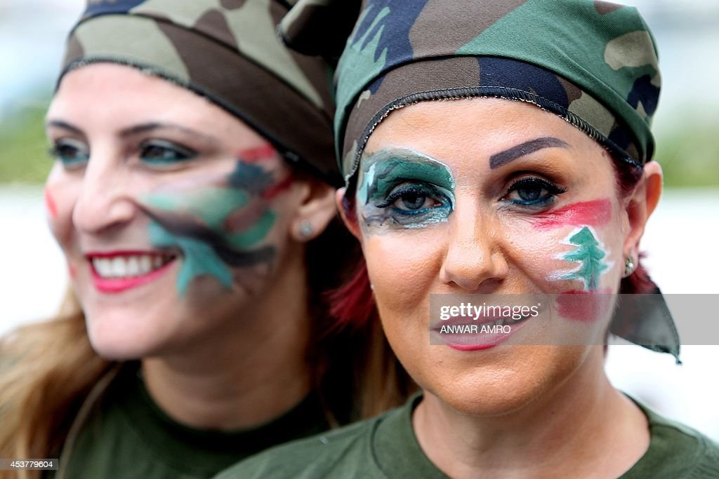 Lebanese women dressed in military fatigue and their faces painted with the colours of their national flag hold a sit in at Martyrs square in...