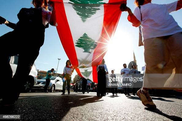 Lebanese women hold national flags during a demonstration in downtown Beirut denouncing the ongoing rubbish crisis and political gridlock on November...