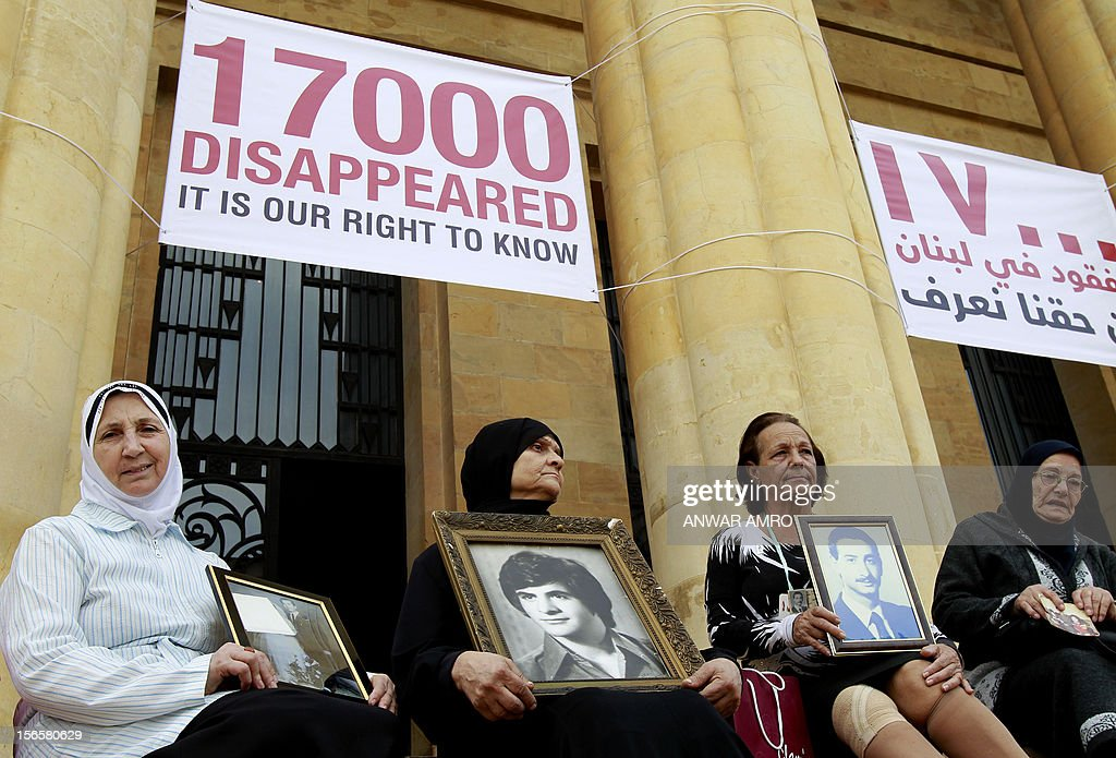 Lebanese women hold the images of missing loved ones as they rally outside the National Museum which stood along the demarcation line known as the 'Green Line' marking the division between east and west Beirut on November 17, 2012. Participants marched along a route linking the Mathhaf area of Beirut, where a large number of disappearances took place, to three neighbourhoods where the state has recognised the presence of mass graves.