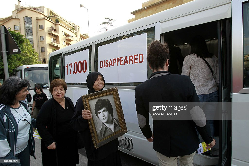 Lebanese women hold the images of missing loved ones get on a bus outside the National Museum which stood along the demarcation line known as the 'Green Line' marking the division between east and west Beirut on November 17, 2012. Participants marched along a route linking the Mathhaf area of Beirut, where a large number of disappearances took place, to three neighbourhoods where the state has recognised the presence of mass graves. AFP PHOTO/ANWAR AMRO