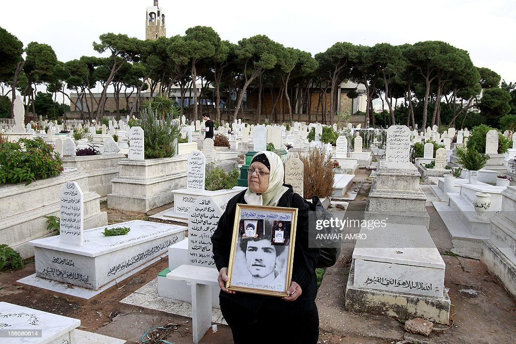 A Lebanese women holds an image of her missing son in a cemetery in the Beirut southern suburb of Qasqas on November 17, 2012 which is one of three neighbourhoods where the Lebanese state has recognised the presence of mass graves. Some 300 people rallied in the Lebanese capital, commemorating 17,000 people who were disappeared during the country's 15-year civil war, while calling for action on behalf of victims' families, organisers and participants said. AFP PHOTO/ANWAR AMRO