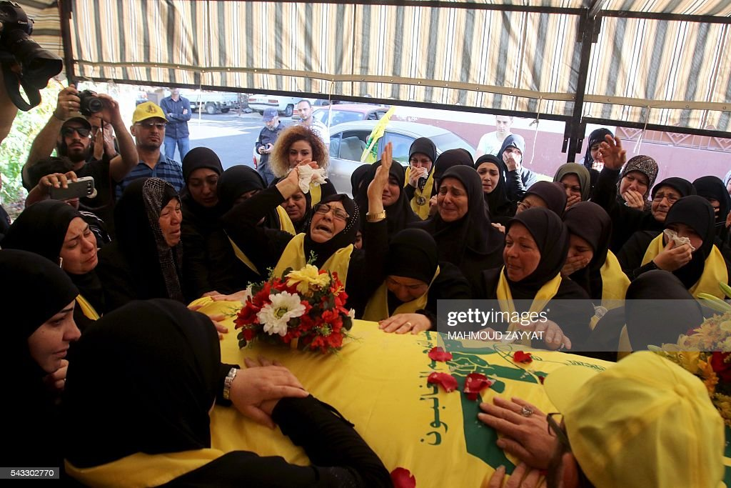 Lebanese women mourn next to the coffin of Mohammed Ibrahim Hamza, a member of Lebanon's militant Shiite Muslim movement Hezbollah who was killed in combat alongside Syrian government forces, during his funeral on June 27, 2016 in the southern Lebanese town of Sharqiyeh. / AFP / MAHMOUD