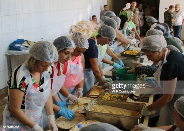 Lebanese women prepare food for fighters from the Lebanese army combating the Islamic State group on the country's eastern border at a kitchen near...