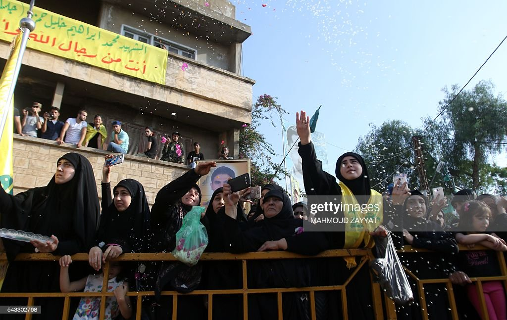 Lebanese women throw flowers during the funeral of Mohammed Ibrahim Hamza, a member of Lebanon's militant Shiite Muslim movement Hezbollah who was killed in combat alongside Syrian government forces, on June 27, 2016 in the southern Lebanese town of Sharqiyeh. / AFP / MAHMOUD