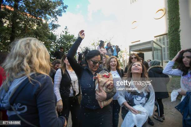 Lebanese women throw rice in celebration as Prime Minister Saad Hariri makes a public appearance at his home 'Beit alWasat' November 22 2017 in...