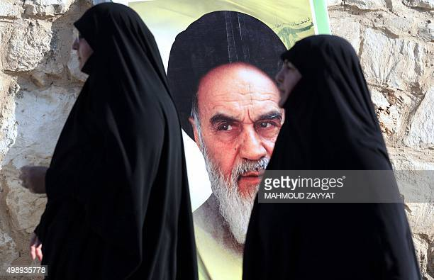 Lebanese women walk past a portrait of the founder of Iran's Islamic Republic Ayatollah Ruhollah Khomeini in the southern Lebanese city of Saksakieh...