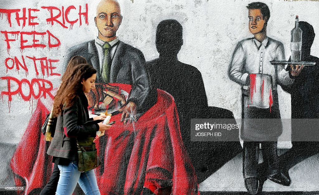 Lebanese women walk past graffiti painted on a wall in the capital Beirut on December 2, 2014. AFP PHOTO / JOSEPH EID