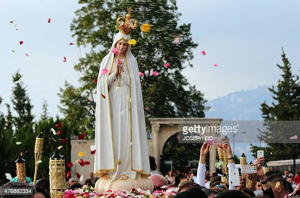 Lebanese worshipers carry the statue of Our Lady of Fatima as they walk to the Maronite patriarchate in Bkerke on June 12 2015 The sacred statue will...