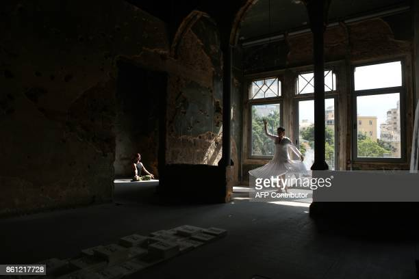 Lebanese Yogi Danielle Abi Saab practises Yoga while local artist Zena elKhalil spins like a Dervish in Beit Beirut on October 14 during an...