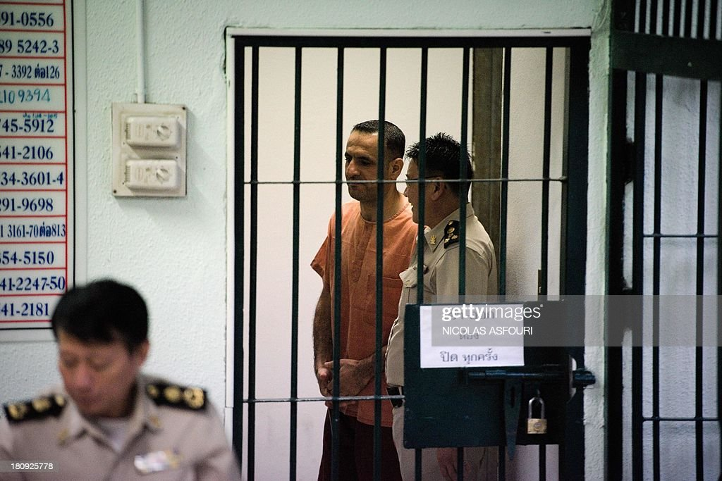 Lebanese-Swedish man Atris Hussein (C) leaves a holding cell for the courtroom at the criminal court in Bangkok on September 18, 2013. Thailand sentenced the Swedish citizen of Lebanese origin to two years and eight months in prison for possession of materials that could be used to make a bomb. AFP PHOTO/ Nicolas ASFOURI