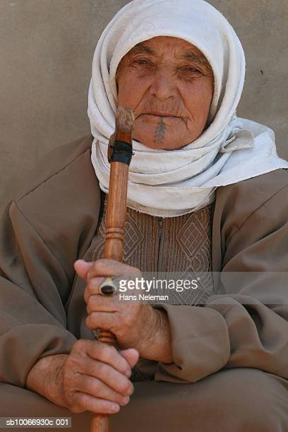 Lebanon, Beirut, Senior woman with face tattoo holding musical instrument, close-up, portrait