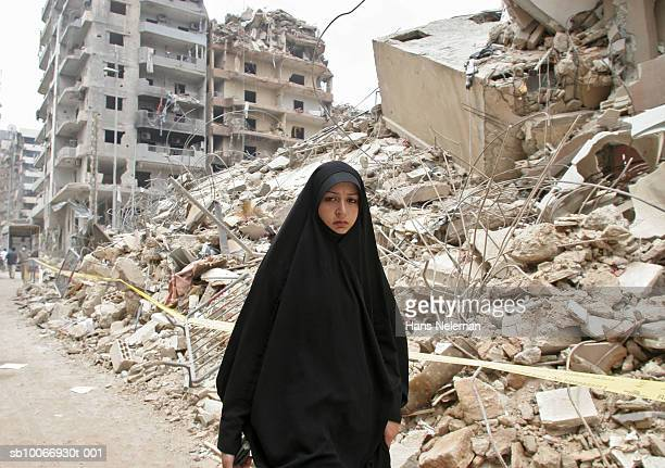 Lebanon, Beirut, Young woman walking through ruins of city destroyed by war