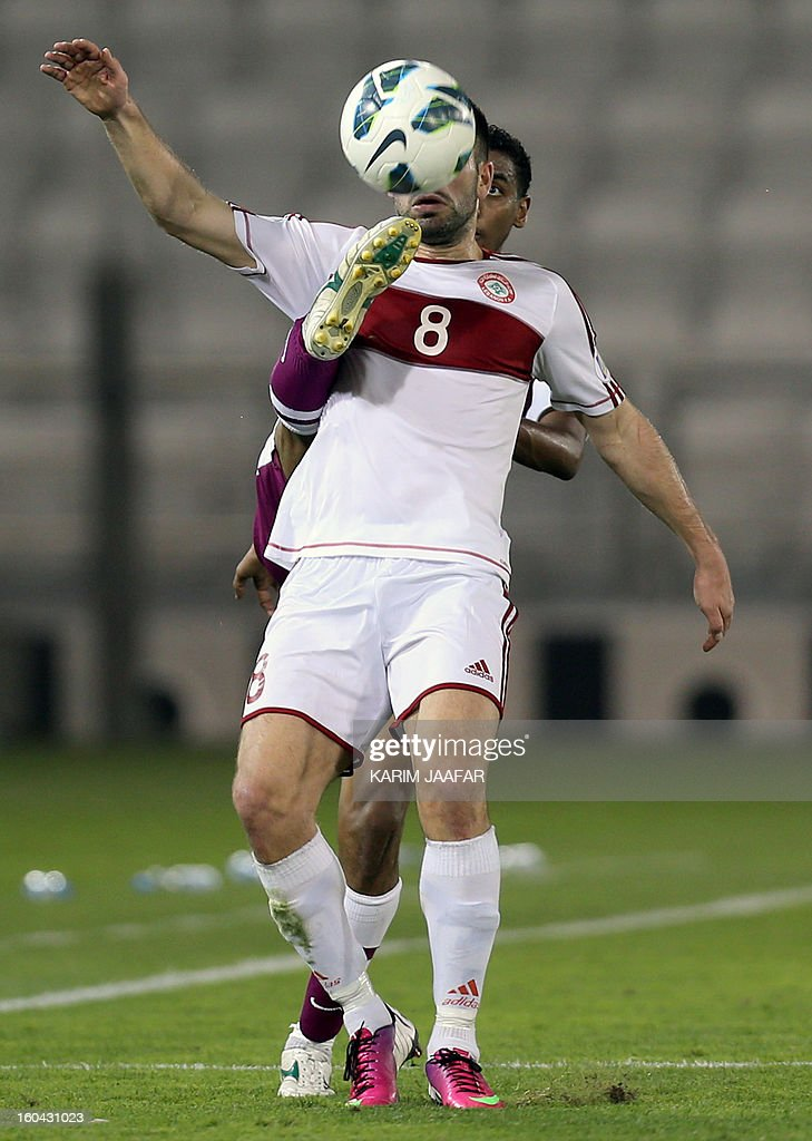Lebanon's Adnan Haidar (front) fights for the ball with Qatar's Mohammed Al-Sayed Jedo during their friendly football match in Doha January 31, 2013. Qatar won the match 1-0.