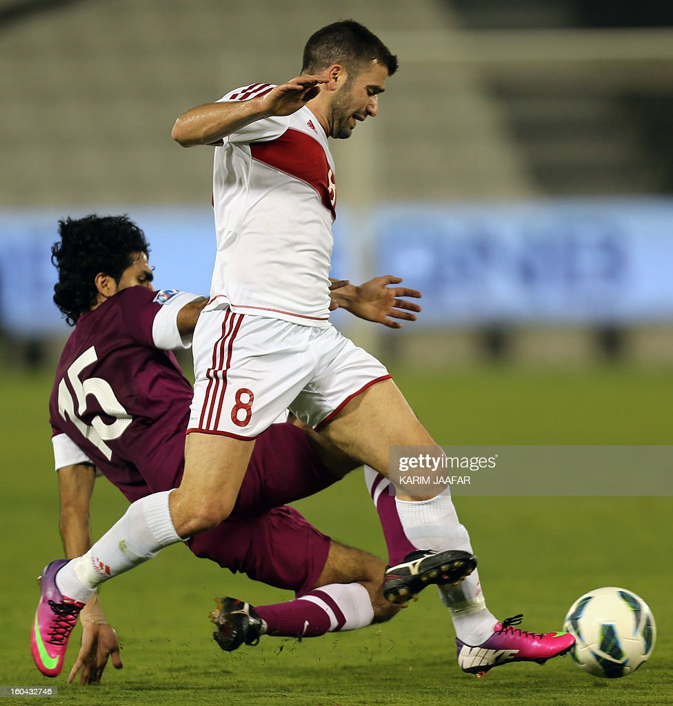 Lebanon's Adnan Haidar (front) fights for the ball with Qatar's Talal al-Bloshi during their friendly football match in Doha January 31, 2013. Qatar won the match 1-0.