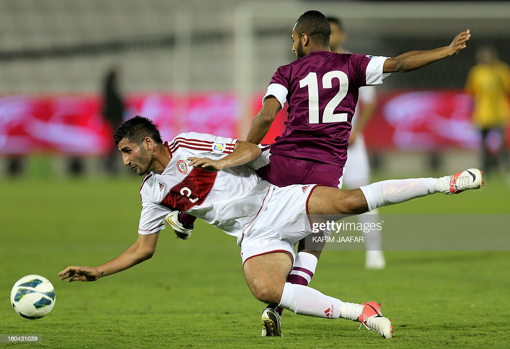 Lebanon's Ali al-Saadi (front) fights for the ball with Qatar's Majed Mohammed during their friendly football match in Doha January 31, 2013. Qatar won the match 1-0.