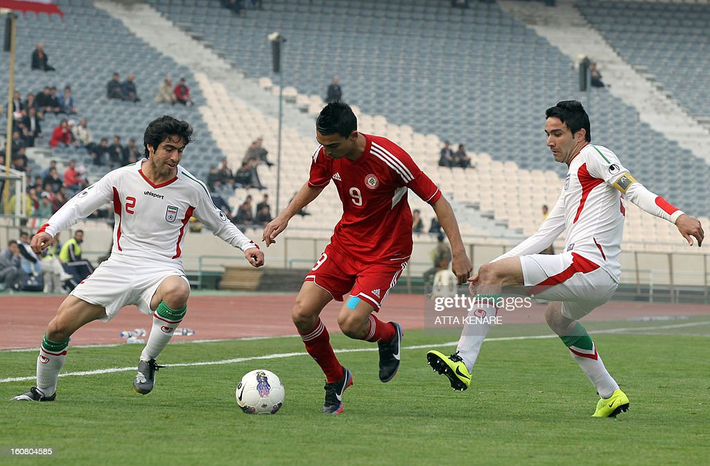 Lebanon's Mohammed Haidar (C) fights for the ball against Javad Nekoonam (R) and Khosro Heidari (L) of Iran during their 2015 AFC Asian Cup group B qualifying football match at the Azadi Stadium in Tehran, on February 3, 2013 Iran won the match 5-0. AFP PHOTO/ATTA KENARE