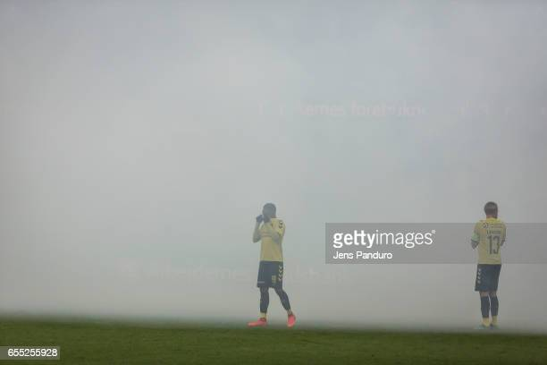 Lebogang Phiri of Brondby IF and Johan Larsson of Brondby IF in the fog from flares lit by supporters the Danish Alka Superliga match between Brondby...