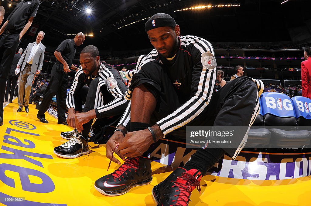 LeBron James #6 and Dwyane Wade #3 of the Miami Heat lace up their shoes before facing the Los Angeles Lakers at Staples Center on January 15, 2013 in Los Angeles, California.