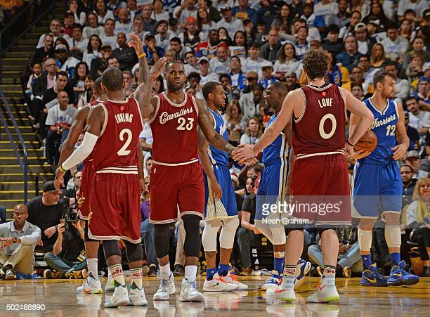 LeBron James and Kevin Love and Kyrie Irving of the Cleveland Cavaliers shake hands on against the Golden State Warriors on December 25 2015 at...