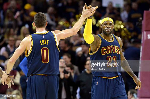 LeBron James and Kevin Love of the Cleveland Cavaliers react after a play in the first quarter at Quicken Loans Arena on October 30 2014 in Cleveland...