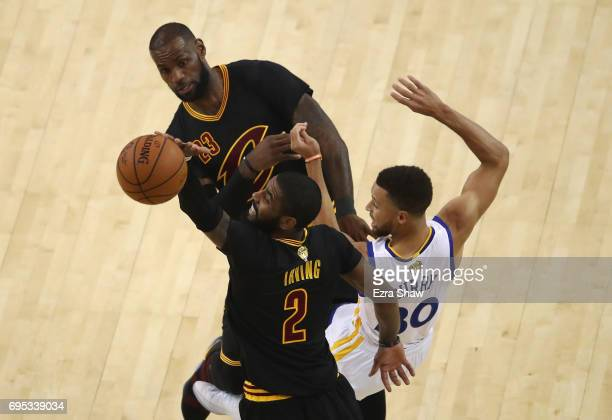 LeBron James and Kyrie Irving of the Cleveland Cavaliers and Stephen Curry of the Golden State Warriors go for a loose ball in Game 5 of the 2017 NBA...