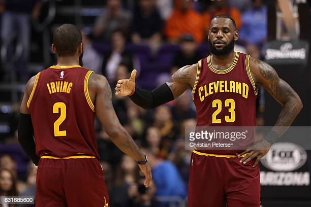 LeBron James and Kyrie Irving of the Cleveland Cavaliers high five during the NBA game against the Phoenix Suns at Talking Stick Resort Arena on...