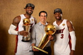 LeBron James Head Coach Erik Spoelstra and Dwyane Wade of the Miami Heat poses for a portrait with the Larry O'Brien Trophy after defeating the San...
