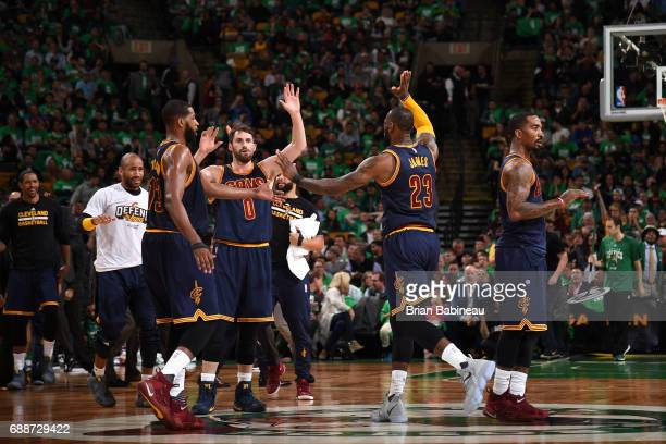 LeBron James high fives Kevin Love and Tristan Thompson of the Cleveland Cavaliers during the game against the Boston Celtics in Game Five of the...