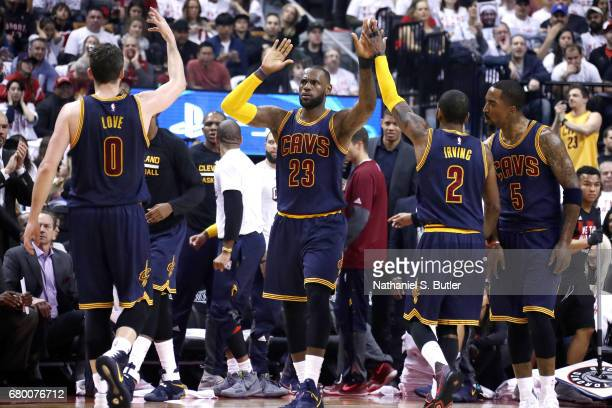 LeBron James Kevin Love and Kyrie Irving of the Cleveland Cavaliers high five each other during the game against the Toronto Raptors in Game Four of...