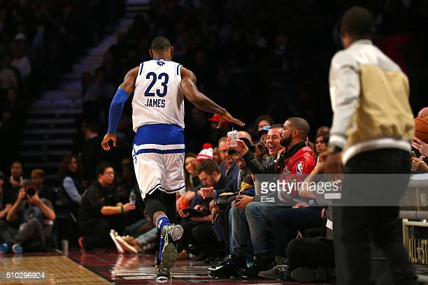 LeBron James of the Cleveland Cavaliers and the Eastern Conference takes a drink from actor Kevin Hart and hands it to rapper Drake in the second...