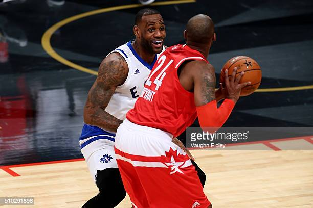 LeBron James of the Cleveland Cavaliers and the Eastern Conference smiles as he defends Kobe Bryant of the Los Angeles Lakers and the Western...