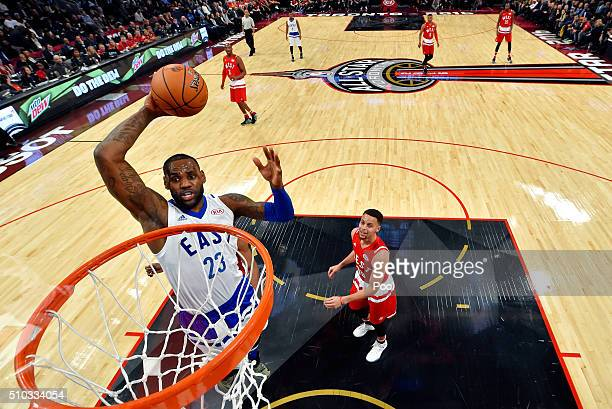 LeBron James of the Cleveland Cavaliers and the Eastern Conference goes up for a dunk in the first half against Stephen Curry of the Golden State...