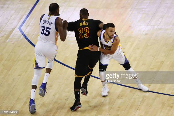 LeBron James of the Cleveland Cavaliers attempts to run past Kevin Durant and Stephen Curry of the Golden State Warriors during the second half of...