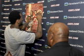 LeBron James of the Cleveland Cavaliers autographs a large copy of the Sports Illustrated Lakeside Legends Special Issue cover that he and Cleveland...