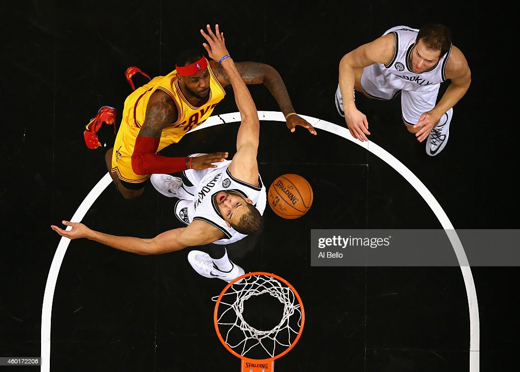 LeBron James #23 of the Cleveland Cavaliers battles Jerome Jordan #9, and Bojan Bogdanovic #44 of the Brooklyn Nets during their game at the Barclays Center on December 8, 2014 in New York City.