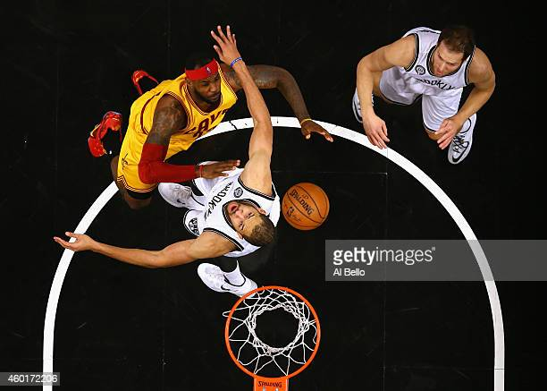 LeBron James of the Cleveland Cavaliers battles Jerome Jordan and Bojan Bogdanovic of the Brooklyn Nets during their game at the Barclays Center on...