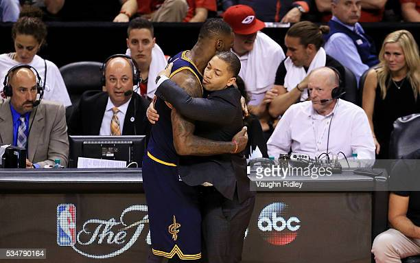 LeBron James of the Cleveland Cavaliers celebrates their 113 to 87 win over the Toronto Raptors with head coach Tyronn Lue in game six of the Eastern...
