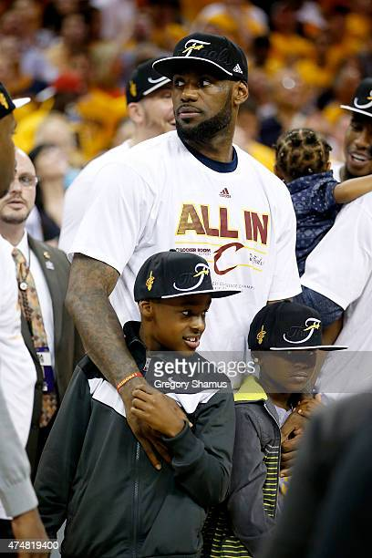 LeBron James of the Cleveland Cavaliers celebrates with his sons LeBron Jr and Bryce Maximus after defeating the Atlanta Hawks during Game Four of...