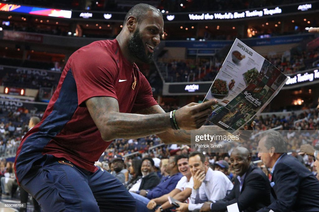 LeBron James #23 of the Cleveland Cavaliers celebrates with teammates as he looks at a Greene Turtle restaurant menu after teammate Jeff Green #32 (not pictured) dunked in the first half during a preseason game at Capital One Arena on October 8, 2017 in Washington, DC.