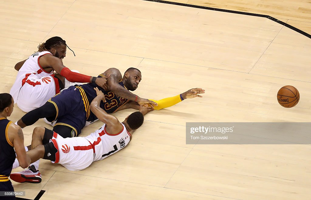 LeBron James #23 of the Cleveland Cavaliers competes for a loose ball late in the game against DeMarre Carroll #5 and Kyle Lowry #7 of the Toronto Raptors in game four of the Eastern Conference Finals during the 2016 NBA Playoffs at the Air Canada Centre on May 23, 2016 in Toronto, Ontario, Canada.