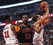 LeBron James of the Cleveland Cavaliers complains to a referee as he is trapped between Jimmy Butler and Joakim Noah of the Chicago Bulls during the...